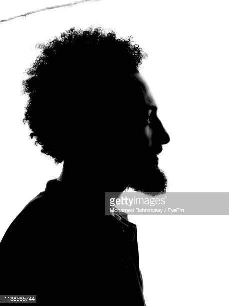 side view of silhouette young man standing against white background - belichting stockfoto's en -beelden