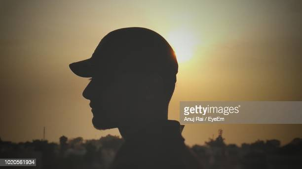 Side View Of Silhouette Young Man Wearing Cap Against Sky During Sunset