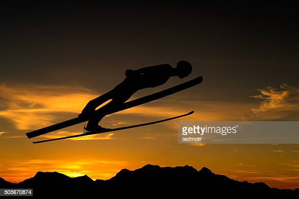 side view of ski jumper in mid-air against the sunlight - ski jumping stock pictures, royalty-free photos & images