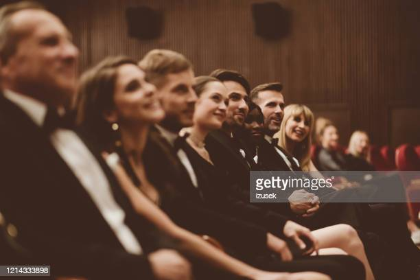 side view of smiling audience sitting in the theater - formal stock pictures, royalty-free photos & images