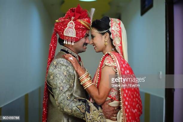 side view of smiling bride and groom standing in room - indian bride stock photos and pictures