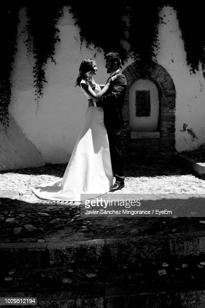 Side View Of Smiling Bride And Groom Standing On Sidewalk Against Building