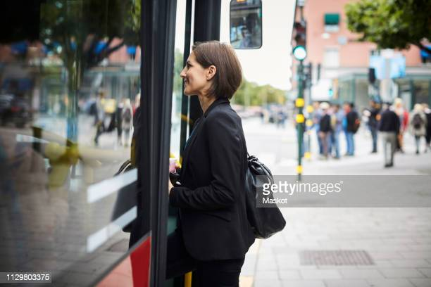 Side view of smiling businesswoman boarding bus in city