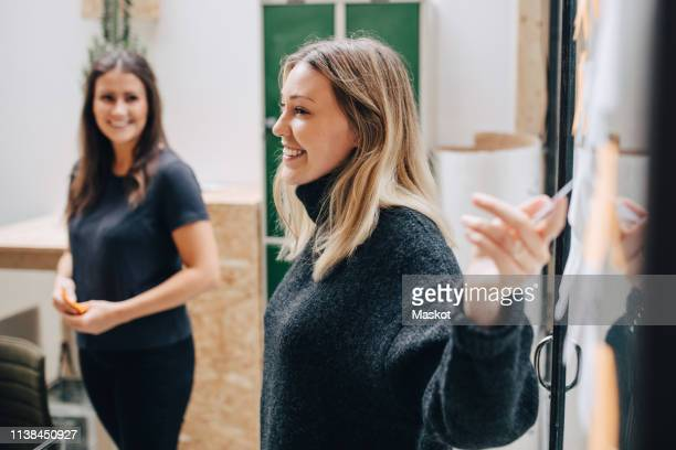 side view of smiling businesswoman explaining adhesive notes stuck on glass wall in meeting - smart casual stock pictures, royalty-free photos & images