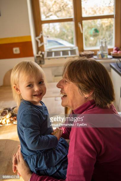 side view of smiling girl with grandmother sitting at home - laughing jesus images stock pictures, royalty-free photos & images
