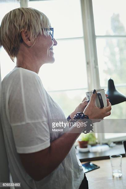 Side view of smiling industrial designer holding coffee cup in kitchen