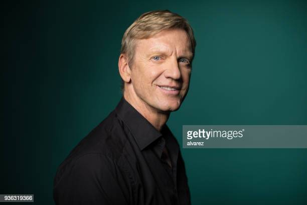 side view of smiling man against green background - formal portrait stock pictures, royalty-free photos & images