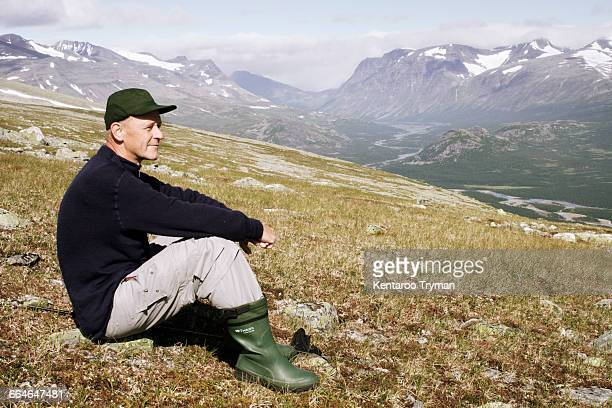 Side view of smiling man sitting on mountain
