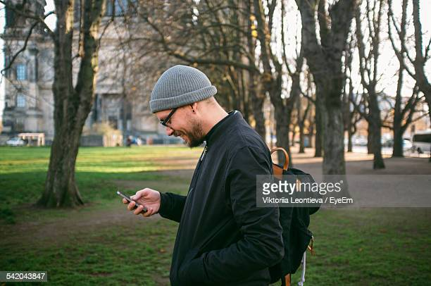 side view of smiling mid adult man using phone in park - ニット帽 ストックフォトと画像