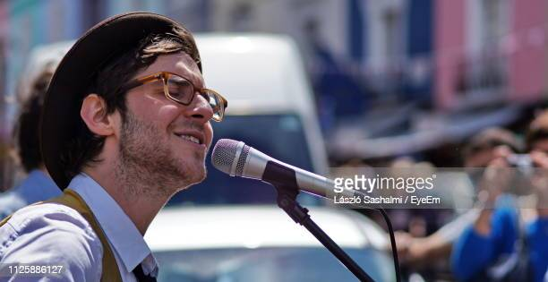 side view of smiling musician singing in city - busker stock pictures, royalty-free photos & images