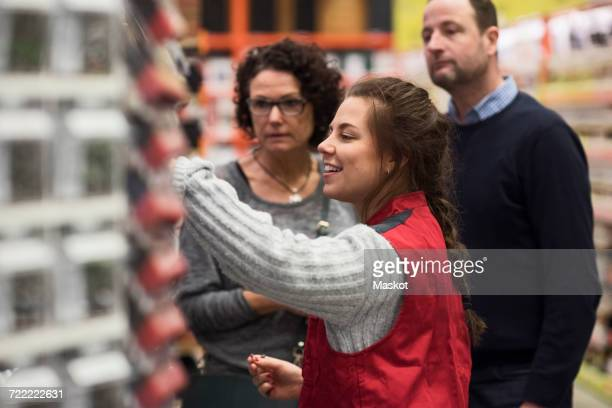 Side view of smiling saleswoman assisting mature couple in hardware store