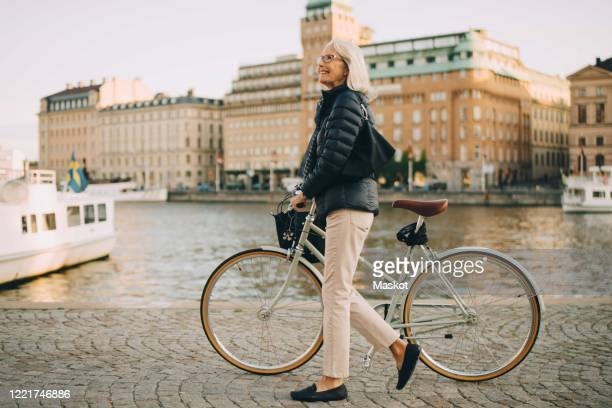 side view of smiling senior woman with bicycle looking up while crossing river in city - stockholm stock pictures, royalty-free photos & images
