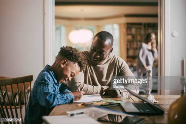 side view of smiling son writing while studying by father over table at home - education stock pictures, royalty-free photos & images