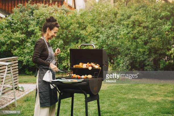 side view of smiling woman cooking dinner on barbecue grill at back yard during garden party - バーベキューグリル ストックフォトと画像