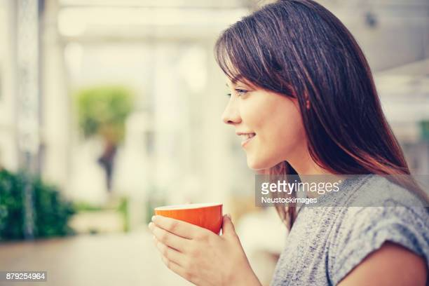 Side view of smiling woman holding coffee mug at cafe