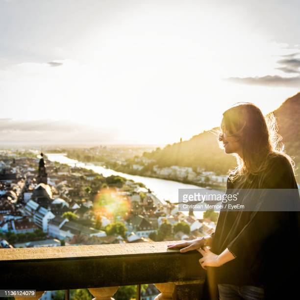 side view of smiling woman looking at city from balcony - baden württemberg stock pictures, royalty-free photos & images