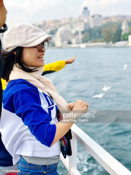 Side View Of Smiling Woman Standing On Boat Sailing In Sea