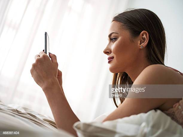 Side view of smiling woman using cell phone in bed.