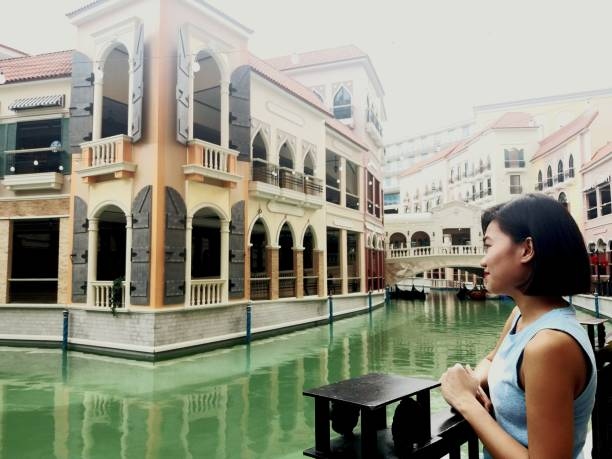 Side View Of Smiling Young Woman By Canal Against Buildings