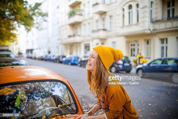 side view of smiling young woman by car on street - city life stock-fotos und bilder