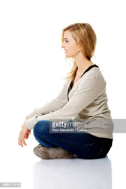 side view of smiling young woman sitting on floor against white background - sitting fotografías e imágenes de stock