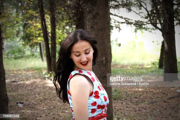 Side View Of Smiling Young Woman Standing In Forest