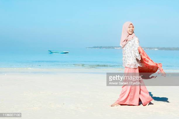 Side View Of Smiling Young Woman Wearing Hijab Walking At Beach Against Clear Blue Sky During Sunny Day