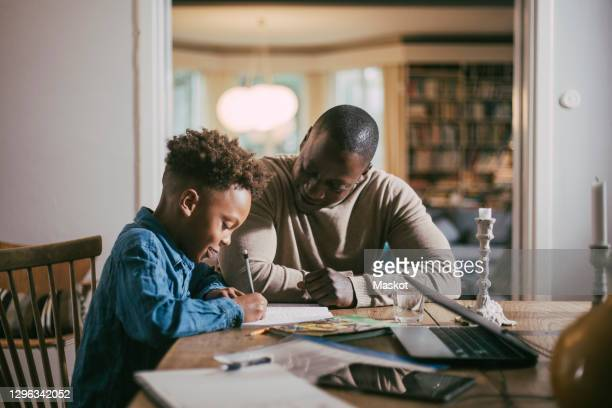 side view of son writing while studying by single father over table at home - homework stock pictures, royalty-free photos & images