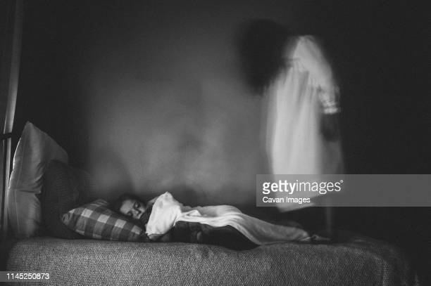 side view of spooky girl standing by sleeping sister on bed against wall at home - ghost stock pictures, royalty-free photos & images