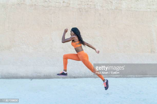 side view of sportswoman jogging by wall - aikāne stock pictures, royalty-free photos & images