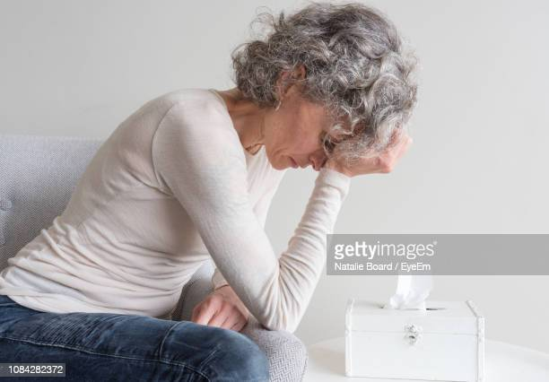 side view of stressed mature woman with head in hand sitting against wall at home - white hair stock pictures, royalty-free photos & images