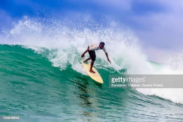 Side view of surfer riding splashing wave, Kuta, Lombok, Indonesia