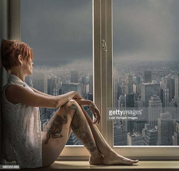 Side view of tattooed mid adult woman in window seat looking out of window at cityscape
