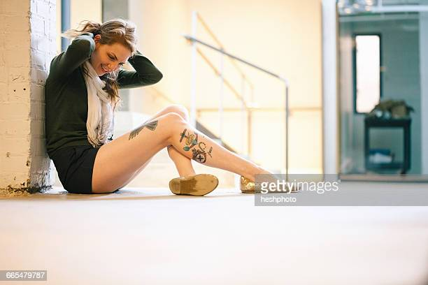 side view of tattooed woman sitting against wall - heshphoto photos et images de collection