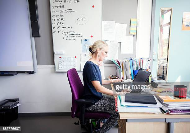 Side view of teacher using laptop in classroom