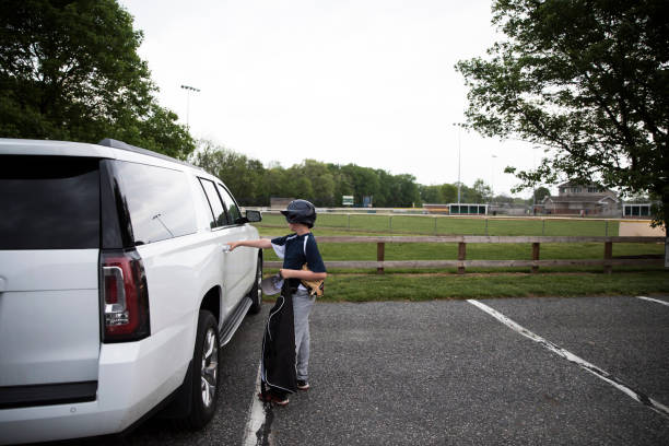 Side View of Teen Boy in Baseball Gear Opening SUV Door After Game
