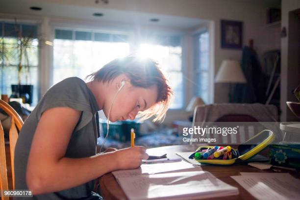 Side view of teenage girl listening music while writing homework at home