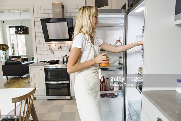 side view of teenage girl looking in refrigerator at domestic kitchen - three quarter length stock pictures, royalty-free photos & images