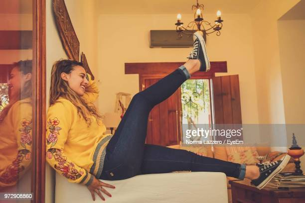 Side View Of Teenage Girl Sitting On Sofa At Home