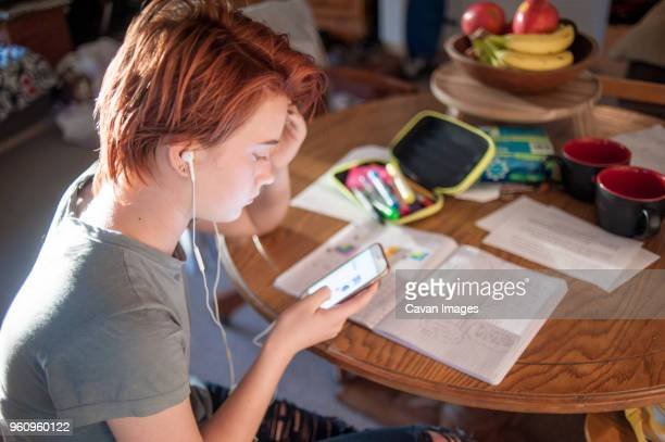 Side view of teenage girl using mobile phone while sitting on chair at home