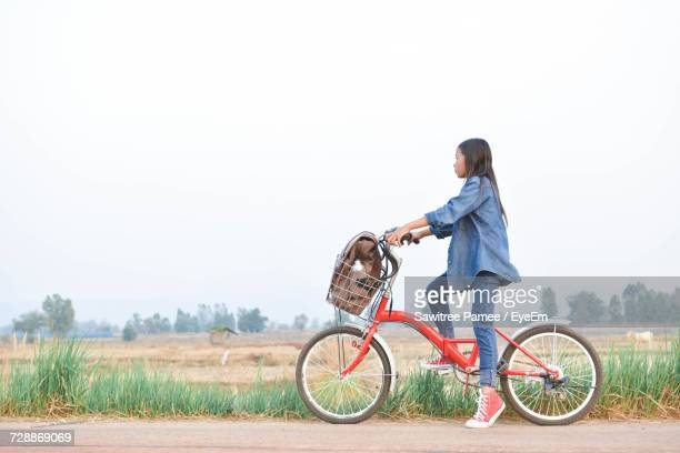 Side View Of Teenage Girl With Bicycle On Roadside By Field Against Clear Sky