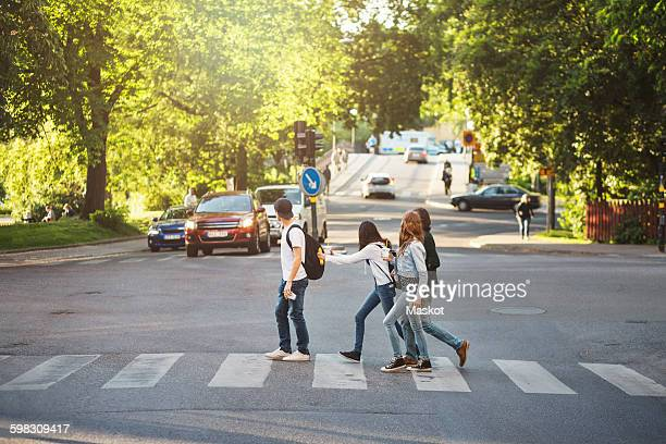 side view of teenagers crossing road - zebra crossing stock pictures, royalty-free photos & images