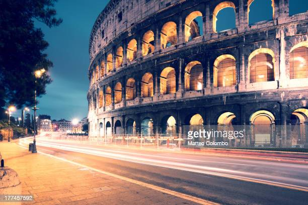Side view of the ancient roman colosseum illuminated at night, with light trails from cars passing on the road. Rome, Italy