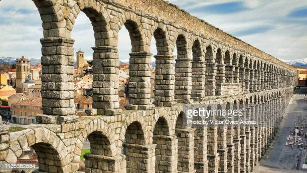 side view of the roman aqueduct (or aqueduct bridge) with the old city in the background in segovia, spain - segovia stock pictures, royalty-free photos & images