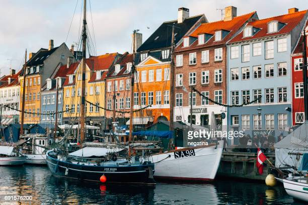 side view of the sailing boats in front of the colorful houses in Nyhavn in Copenhagen, Denmark