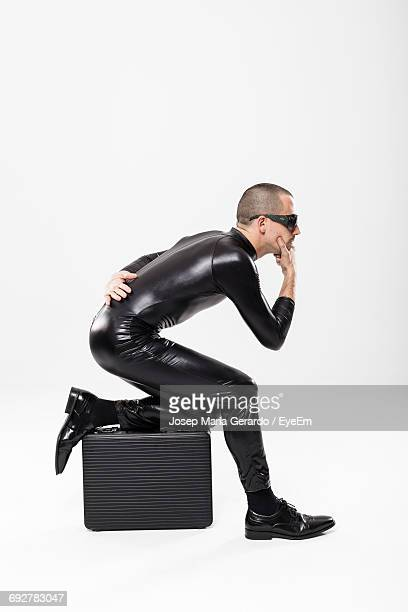 Side View Of Thief With Briefcase Against White Background