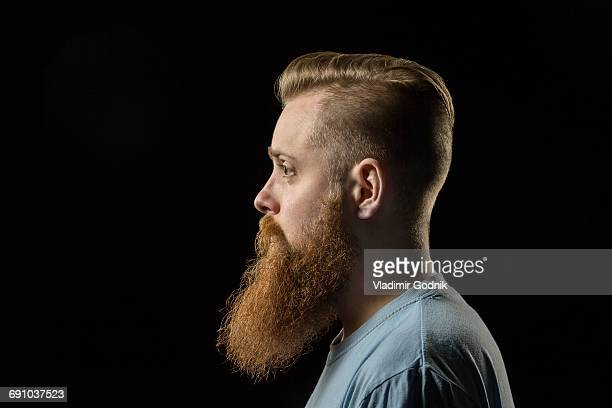 side view of thoughtful bearded man against black background - vollbart stock-fotos und bilder