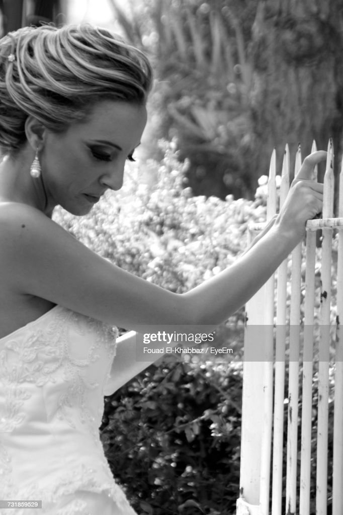 Side View Of Thoughtful Bride Looking Down While Holding Fence At Park : Stock Photo