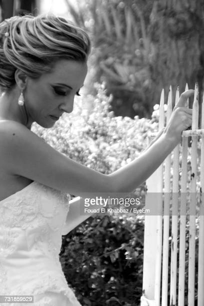 Side View Of Thoughtful Bride Looking Down While Holding Fence At Park