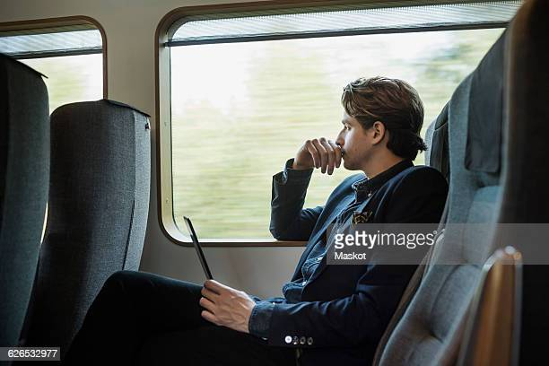 Side view of thoughtful businessman holding digital tablet in train